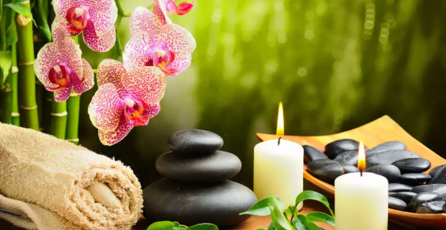 Image of Hot stone massage setting lit by candles - Towel on fern with candles and black hot stone on green background.