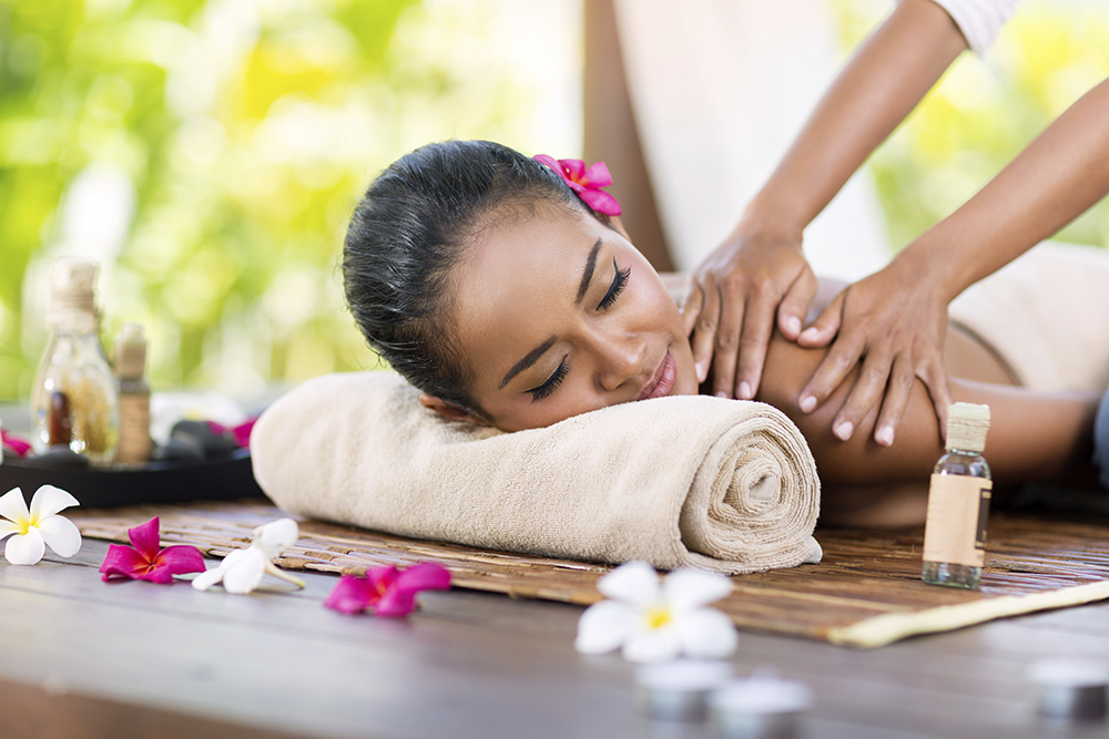 A Woman Experiencing Back Massage By a Professional Massage Therapist in a luxurious massage center.