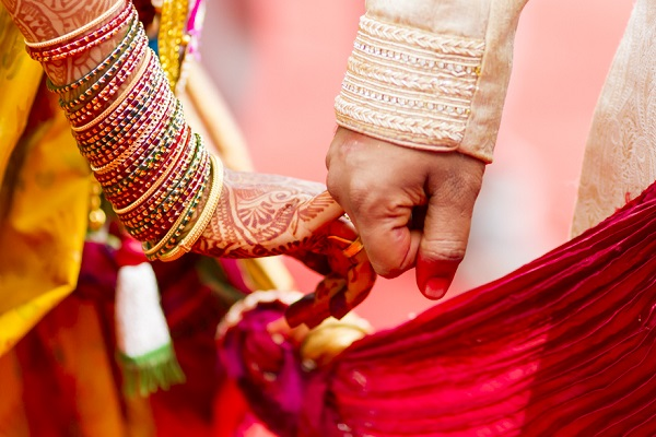A Beautiful Capture of An Indian Bride and Groom Holding Their Hands during the wedding ritual.